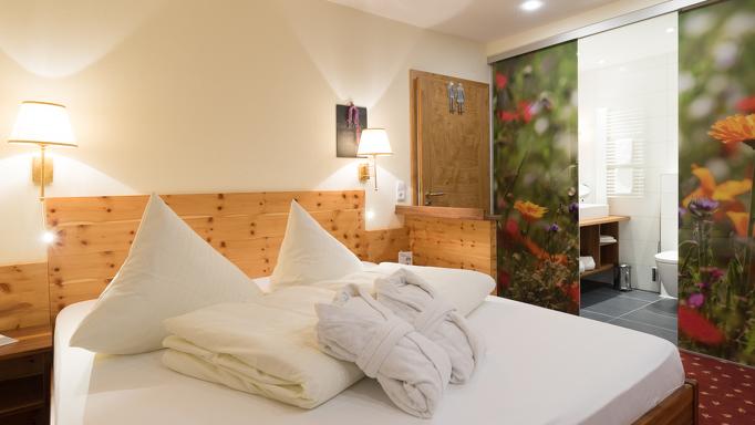 Florale Muster und natürliche Materialien machen das Zimmer im Familienhotel so gemütlich